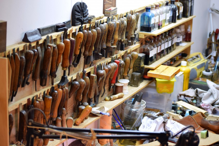 Bespoke workspace wall full of shoemaking tools and leather dyes