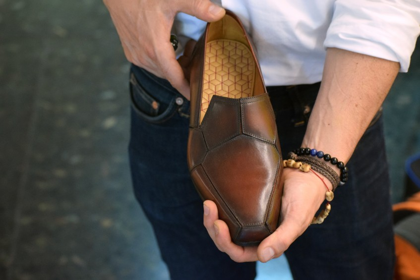 Norman holding his driving loafer, one of his highly innovative designs