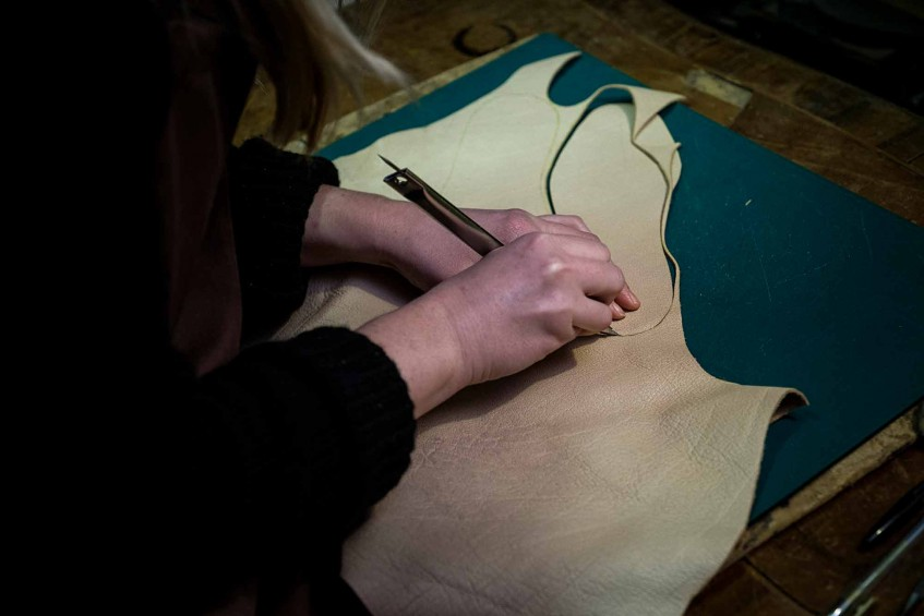 Hand cutting the leathers.